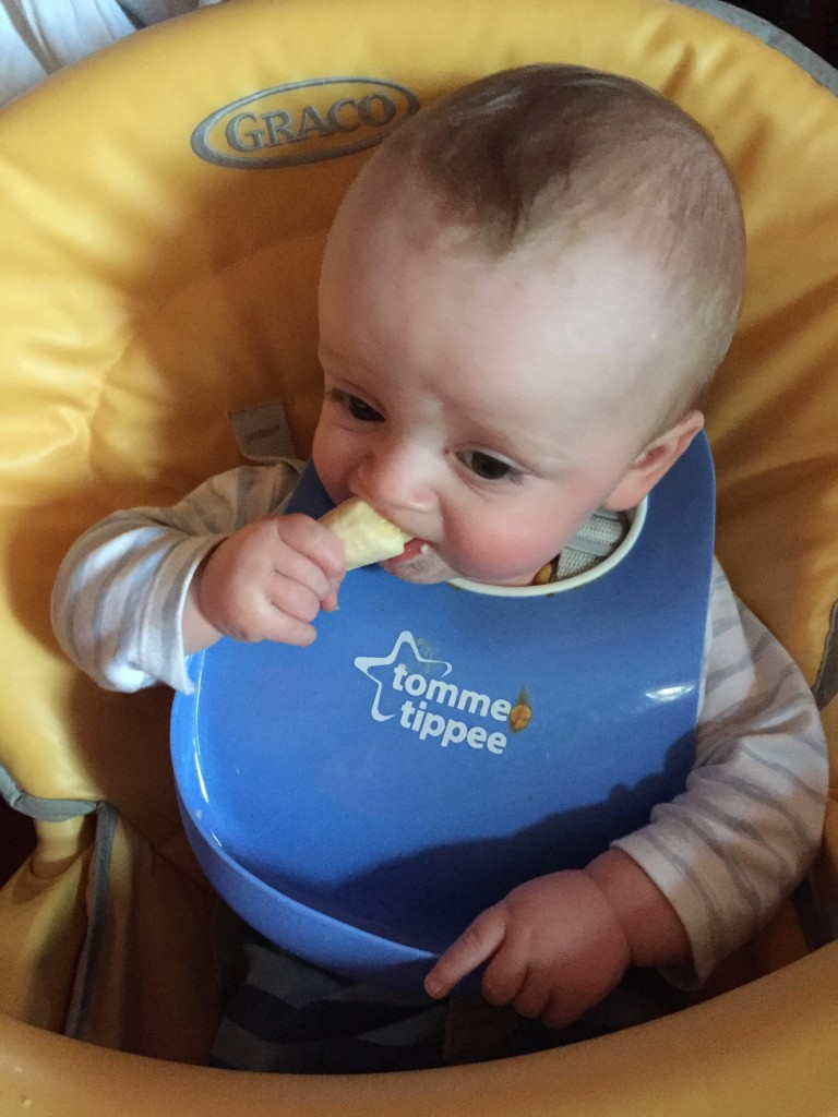 E eating banana with wipe down bib - Essential Baby Products - BadMammy.com